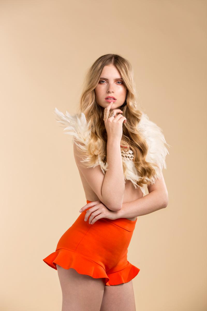 Bondle vrouw met oranje brokje en veren neksierraad