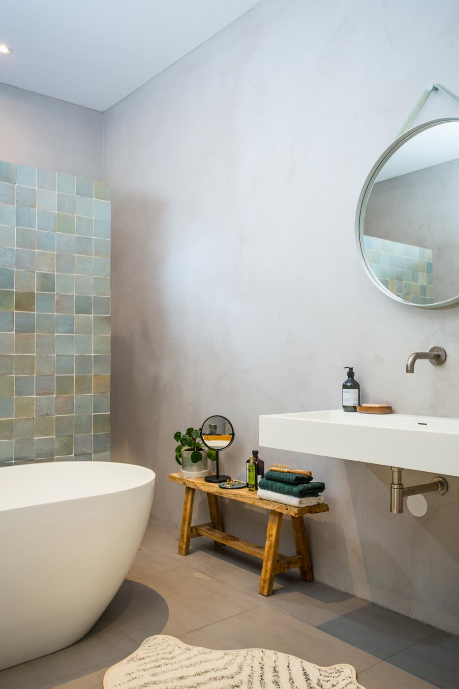badkamer in betonlook met houten krukje met handdoeken en spiegel en plantje. badkuip voor betegelde muur