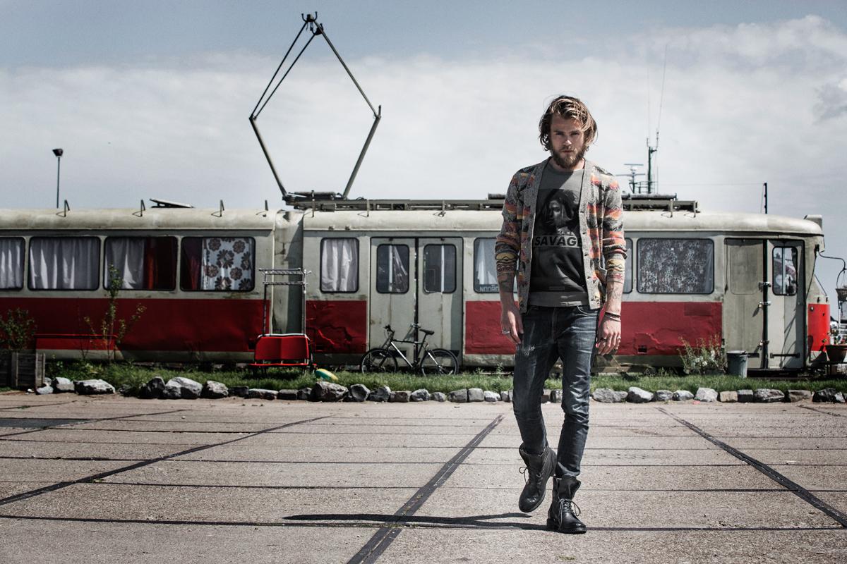 Man met fashion met op d achtergrond een trein