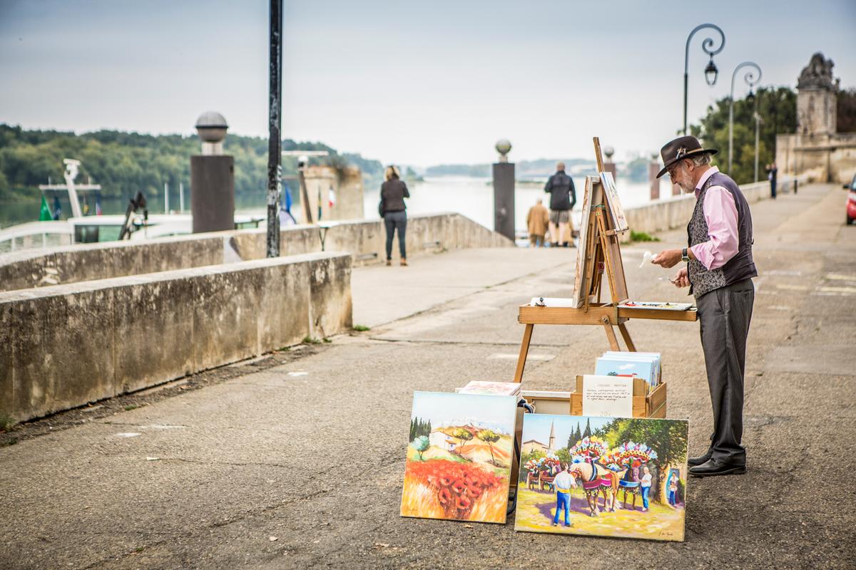 Man die voor het water zit te schilderen
