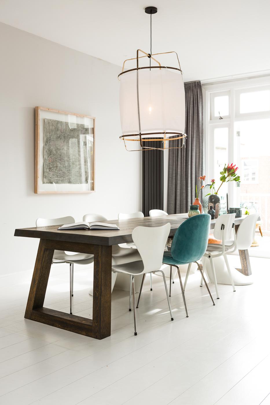 tafel met boek, meerdere soorten stoelen, plantje op tafel, groot raam en schilderij aan muur