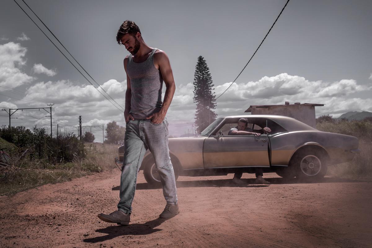 Man in een auto en man die op een zandweg loopt voor de auto
