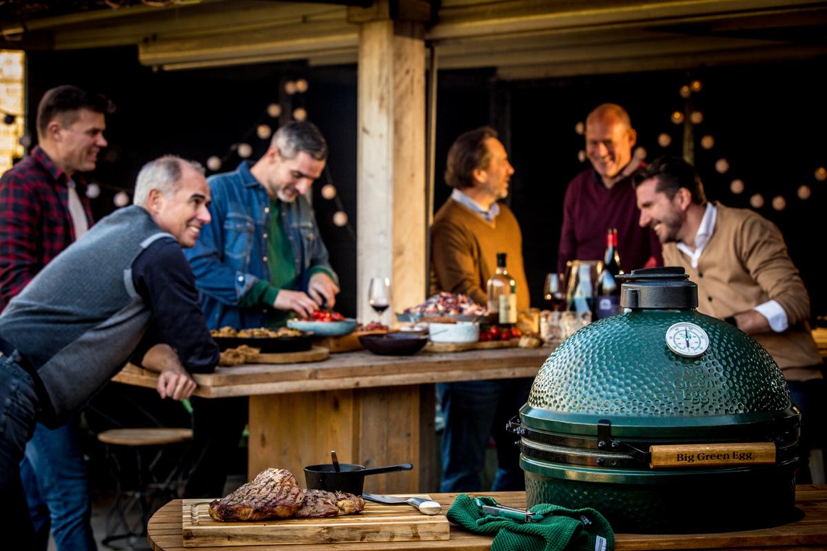 Mannen die in de tuin staan te praten met een tafel vol eten